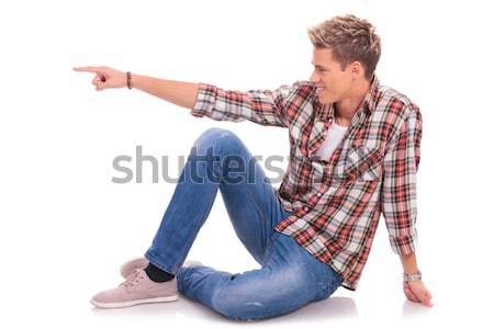 seated young man pointing to side Stock photo © feedough