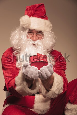 Attractive young santa giving you a small red gift Stock photo © feedough