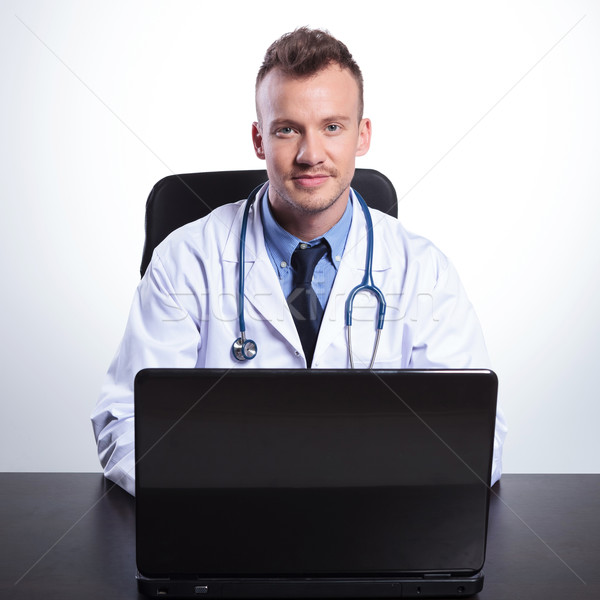 young doctor sitting at his desk  Stock photo © feedough