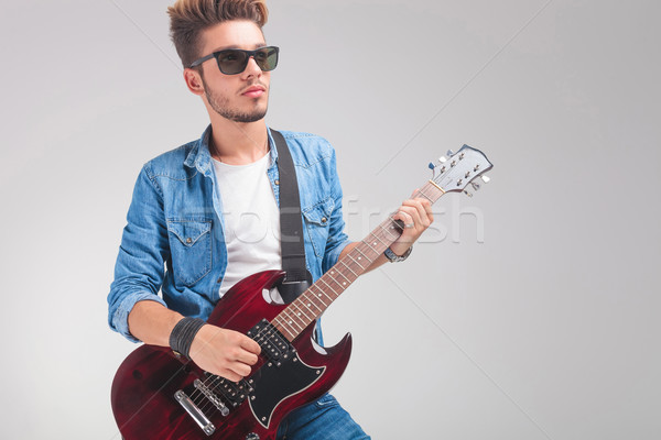 Stock photo: guy wearing sunglasses while playing the guitar