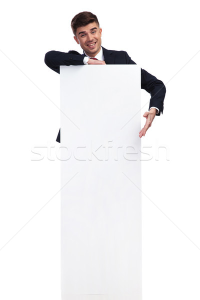 excited businessman presenting while resting an elbow on white b Stock photo © feedough