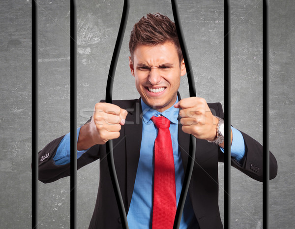 businessman bending the bars of his prison Stock photo © feedough