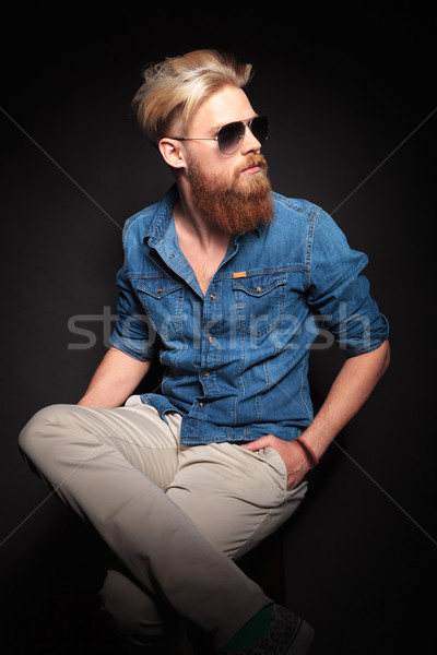 fashion man sitting with his hands in pocket Stock photo © feedough
