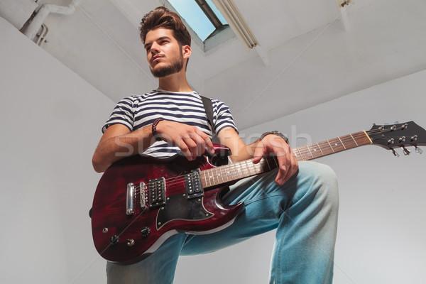 portrait from below upward of young guitarist looking away Stock photo © feedough