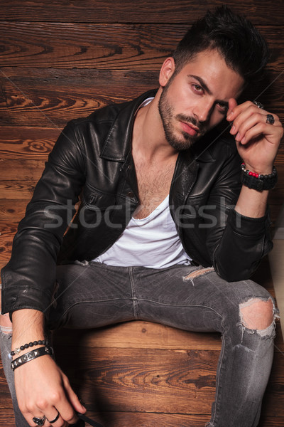 man in leather jacket and jeans sitting on wooden background Stock photo © feedough