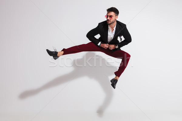 jumping young man parting his legs and unbuttoning black suit Stock photo © feedough