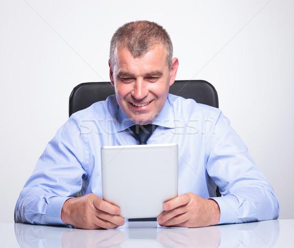 senior business man smiles at his tablet Stock photo © feedough