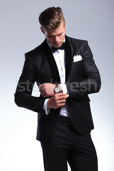 business man looks at his cufflinks Stock photo © feedough