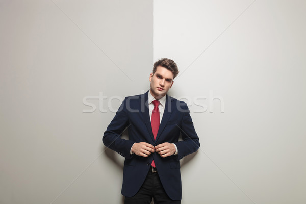 young handsome business man closing his jacket. Stock photo © feedough