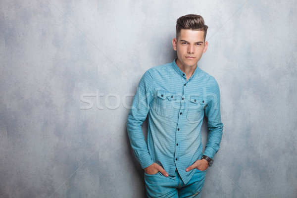 Casual young man leaning on a grey wall. Stock photo © feedough