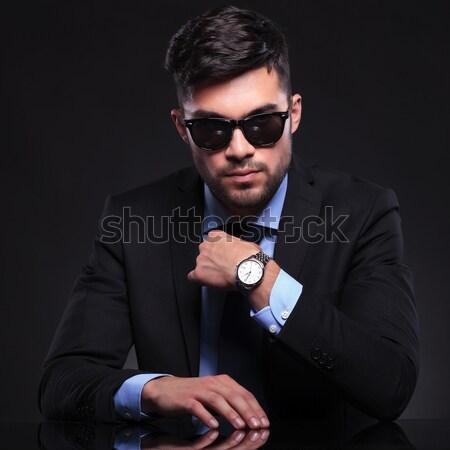 elegant man wearing glasses while fixing his jacket in dark stud Stock photo © feedough
