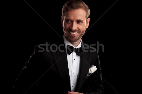 happy elegant man in tuxedo and bowtie looks to side  Stock photo © feedough