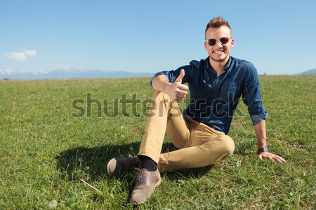 Handsome man posing on a field of grass  Stock photo © feedough