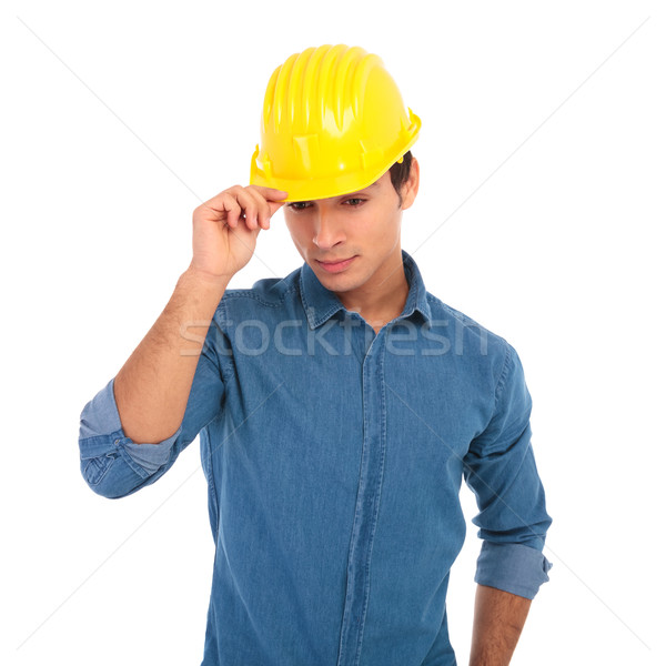 young construction engineer holding his safety helmet and looks  Stock photo © feedough