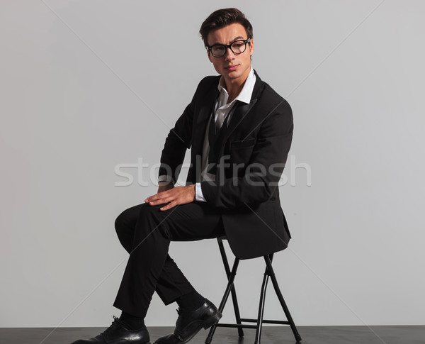 f2dc7615bf3d #8157106 seated man in tuxedo and undone bowtie looks to side by ...
