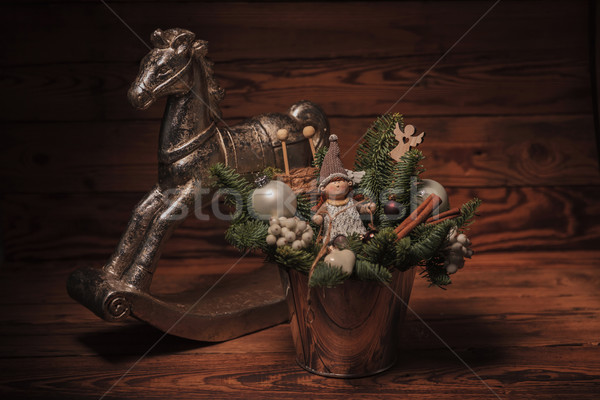 Stock photo: bucket with christmas decorations near toy horse
