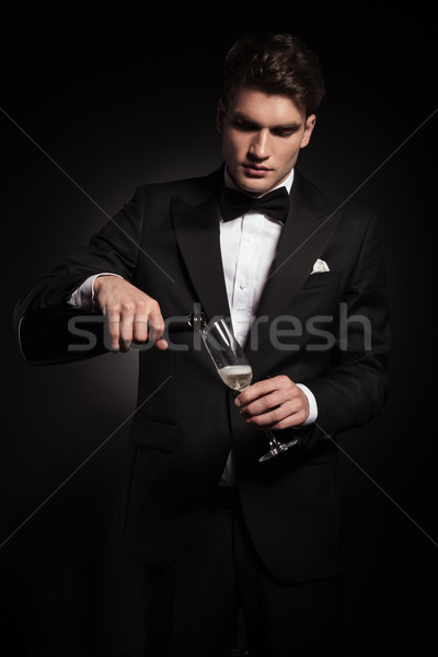 Young elegant man pouring wine in a glass  Stock photo © feedough