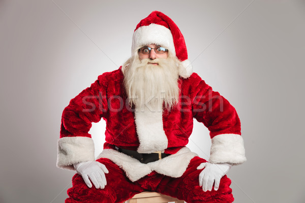 santa claus is sitting and holds hands on knees  Stock photo © feedough