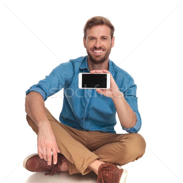 Sentado sonriendo hombre Screen teléfono Foto stock © feedough