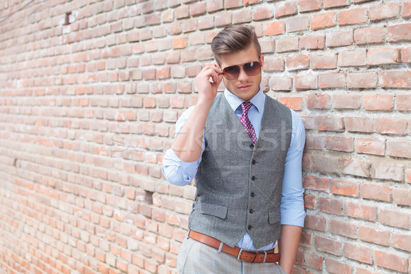 casual man leans on wall and adjust sunglasses Stock photo © feedough