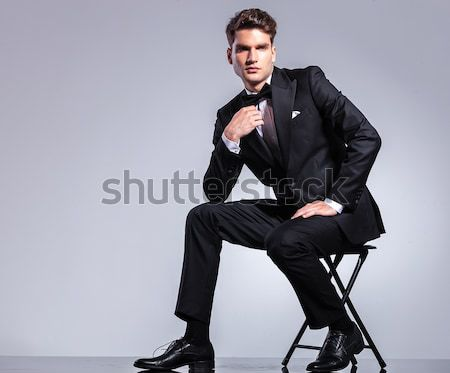 seated young business man looks down with hand on hip Stock photo © feedough