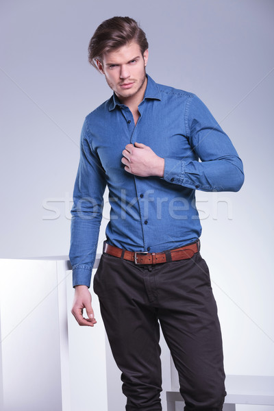 fashion man is unbuttoning his shirt with one hand  Stock photo © feedough