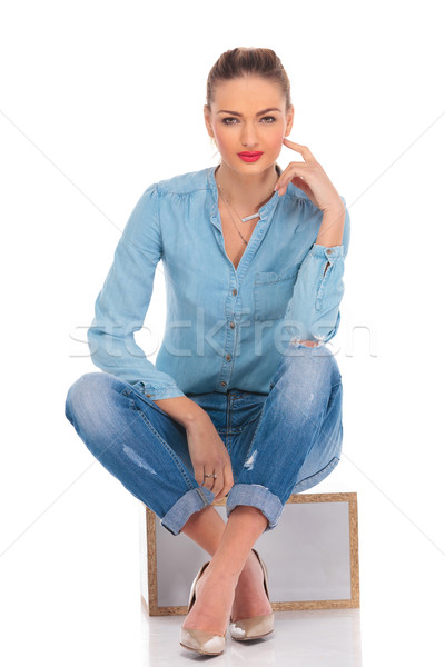 woman pose in studio seated with hand on knee touching face Stock photo © feedough
