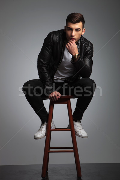 young male in black posing seated on stool in studio Stock photo © feedough