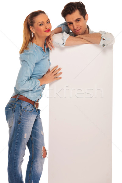 man stands behind billboard while woman rests Stock photo © feedough