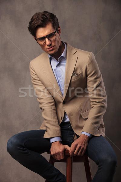 serious fashion model posing seated in studio Stock photo © feedough