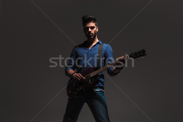 Stock photo: young man standing and playing electric guitar