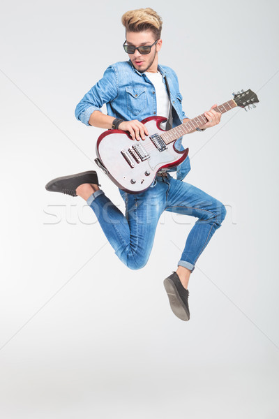 rocker jumping one side in studio while playing guitar Stock photo © feedough