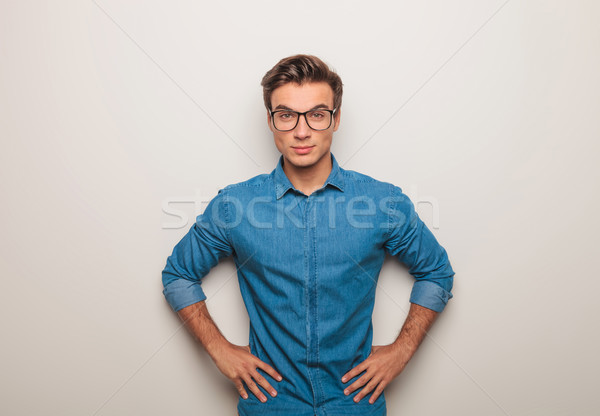 casual young man standing with hands on waist Stock photo © feedough