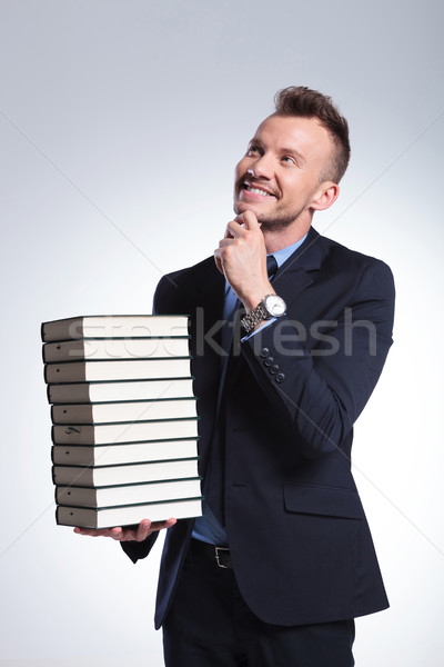 Stock photo: business man holds a pile of books