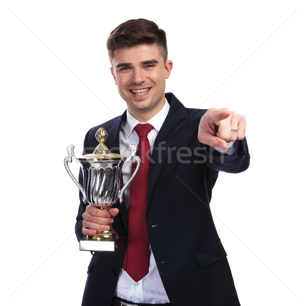 smiling businessman points finger while holding the awarded trop Stock photo © feedough