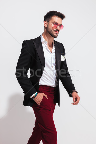 relaxed gentleman wearing black suit and sunglasses walks to sid Stock photo © feedough