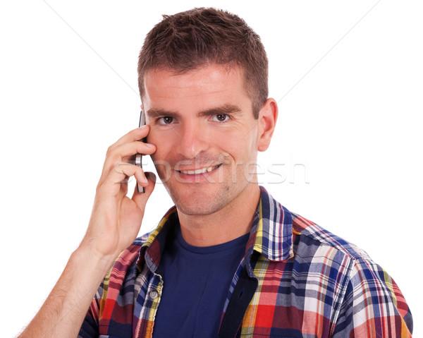 Сток-фото: улыбаясь · молодым · человеком · телефон · случайный · глядя · камеры