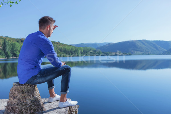 man sits by the lake & looks away Stock photo © feedough