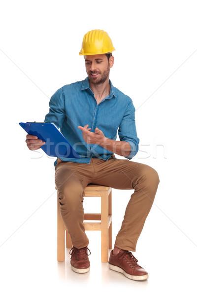 Jeunes assis construction ingénieur pointant presse-papiers Photo stock © feedough