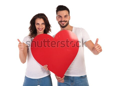 three happy women holding a big red heart pointing fingers  Stock photo © feedough