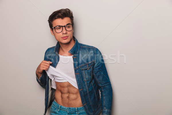 young man  pulls up his undershirt to show his abs Stock photo © feedough