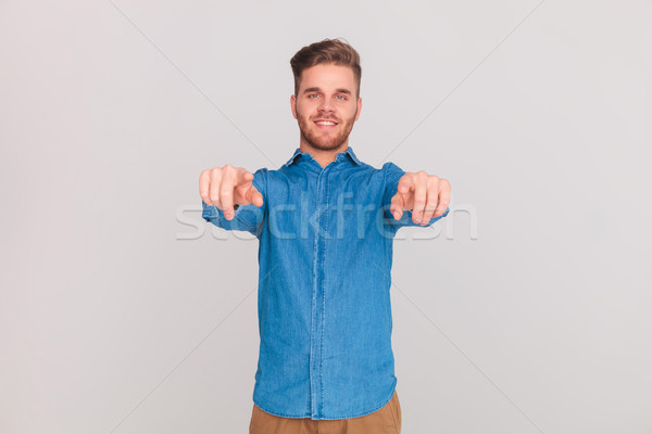 portrait of casual man in blue shirt pointing fingers Stock photo © feedough