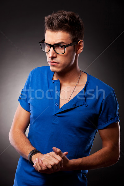 young casual man with hands together and eyebrow raised Stock photo © feedough