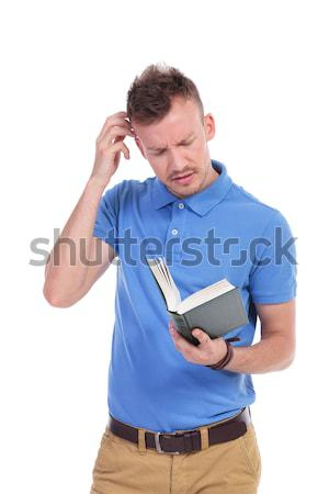 young casual man holds book and thinks Stock photo © feedough