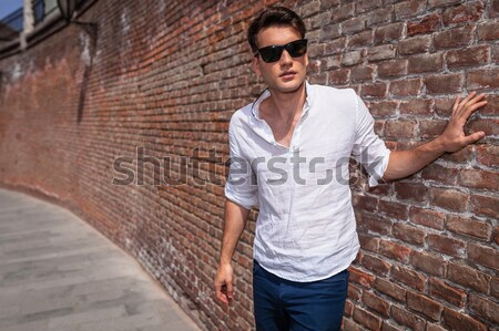 casual man holding his hand on head fixing his hair  Stock photo © feedough