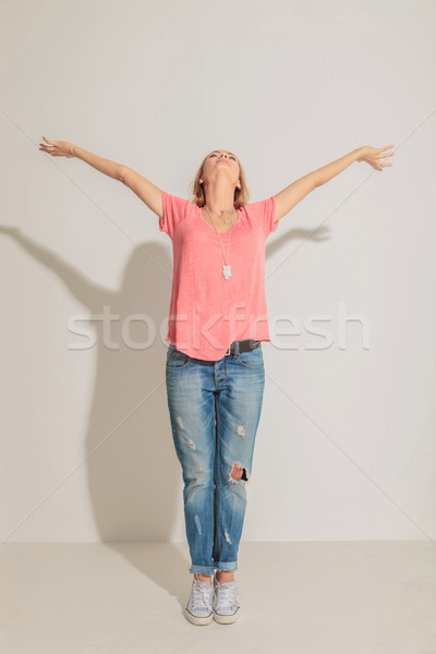 casual woman holding both hand in the up, celebrating. Stock photo © feedough
