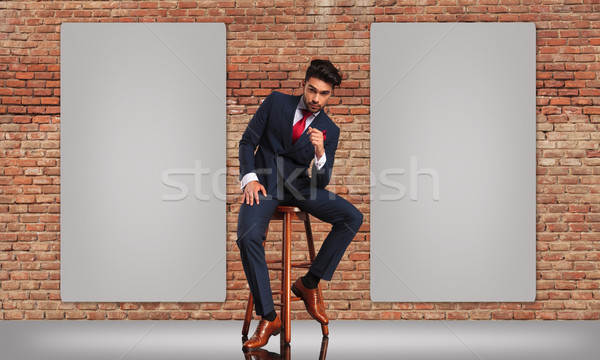 man in double breasted suit sitting near two blank billboards  Stock photo © feedough