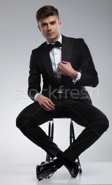 sexy seated elegant man fixing black suit collar Stock photo © feedough