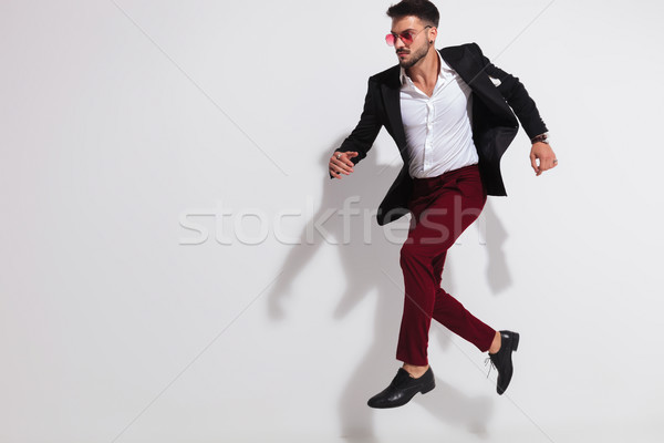elegant man wearing black suit and sunglasses leaping to side  Stock photo © feedough
