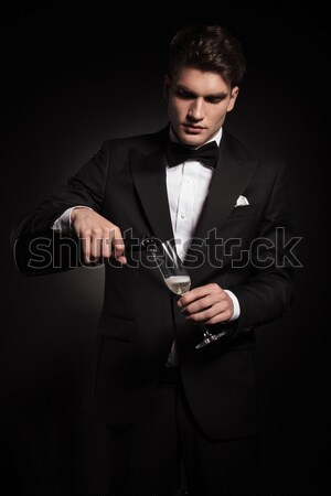 skinny man in black with bowtie posing in dark studio Stock photo © feedough